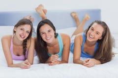 Vänner som tillsammans ligger på säng Arkivfoto