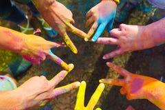 Vänner som tillsammans sätter deras händer i ett tecken av enhet och laget Arkivfoton