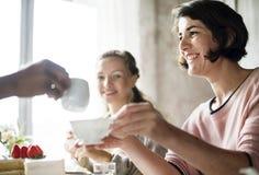 Vänner som tillsammans samlar på tebjudningen som äter kakanjutninglycka arkivfoto