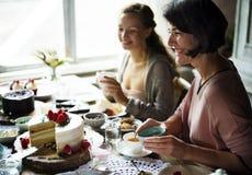 Vänner som tillsammans samlar på tebjudningen som äter kakanjutningH arkivfoton