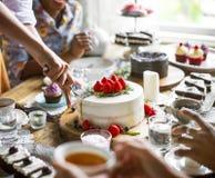 Vänner som tillsammans samlar på tebjudningen som äter kakanjutningH royaltyfri foto