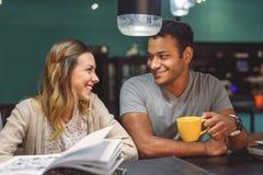 Vänner som tillsammans studerar på coffee shop royaltyfria foton
