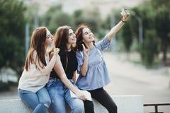 Vänner som tillsammans tar selfie på stadsbakgrund arkivfoto