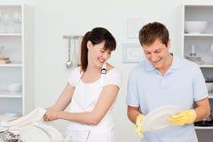 Vänner som tillsammans tvättar disk 免版税库存图片