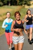 Vänner som tillsammans utomhus joggar den soliga banan Arkivfoton