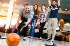 Vänner som tycker om att bowla på klubban Arkivbild