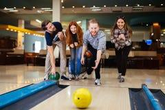 Vänner som tycker om att bowla på klubban Royaltyfri Foto