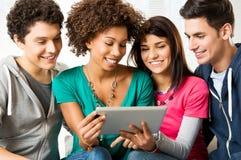 Vänner som tycker om den Digital tableten Arkivfoto