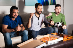 Vänner som tycker om en fotbolllek på tv arkivbilder