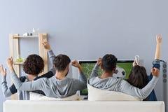 Vänner som tycker om fotboll i TV arkivbild