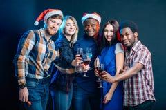 Vänner som tycker om juldrinkar i stång fotografering för bildbyråer