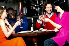 Vänner som tycker om matställen på en restaurang Royaltyfri Fotografi