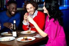 Vänner som tycker om matställen på restaurangen Royaltyfria Bilder