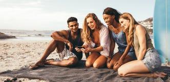 Vänner som tycker om på stranden royaltyfri foto