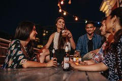Vänner som tycker om partiet med drinkar Royaltyfria Bilder