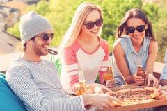 Vänner som tycker om pizza arkivbilder