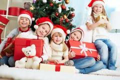 Vänner vid julgranen Royaltyfri Bild