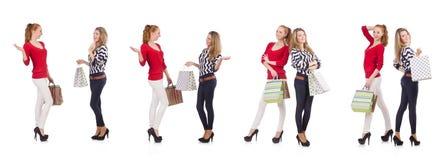 Vännerna med shoppingpåsar som isoleras på vit arkivfoton
