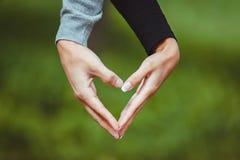 Vänpar som gör en hjärta med händer Fotografering för Bildbyråer