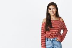 Vänskapsmatch-se den tonårs- flickan för stilfull ung indier i randig blus och jeans som står mot grått le för bakgrund royaltyfria bilder