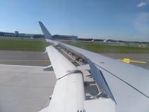 Vänster flygplanvinge på landningsbanan Arkivfoto