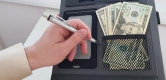 Vänster hand med en penna över svart mapp med dollarsedlar i ett fack arkivbild