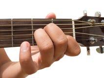 Vänster position för finger för ackord för gitarr för ` för ackord f.m. för ` för handgest i slutet som isoleras upp på vit bakgr arkivbilder
