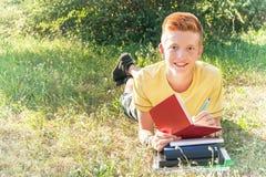 Vänsterhänt tonårigt ligga och skriva på gräset royaltyfri fotografi