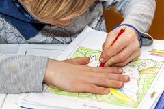 Vänsterhänt ung pojke som arbetar på hans läxa arkivfoton