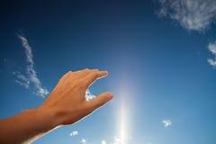 Vänstersidahand som trycker på den blåa himlen med moln Royaltyfri Bild