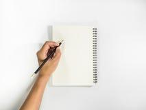 Vänstersidahanden med blyertspennan förbereder sig till att skriva på anteckningsboken Arkivbild