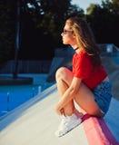 vänta avsked En flicka sitter på rampskridskon parkerar i strålarna av den varma solen Utomhus- sommar royaltyfri fotografi