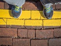 Vänta bak en gul linje Arkivbild