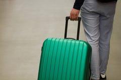 vänta för flygplats Begreppet av sommarsemestern, en handelsresande med en resväska i det väntande området av flygplatsterminalen arkivbild