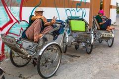 Vänta för Lokal rickshaw av cliens Arkivbilder