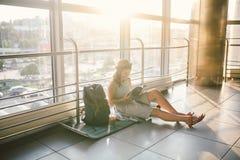 Vänta, försenad transport i terminalen av flygplatsen eller drevstation Den unga caucasian kvinnan i klänning och hatt sitter på  arkivfoton