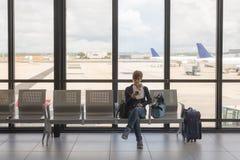 Vänta i flygplatsterminal genom att använda telefonen Arkivbilder