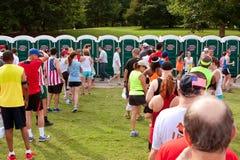 väntan för löpare 10K i linje att använda bärbara toaletter Fotografering för Bildbyråer