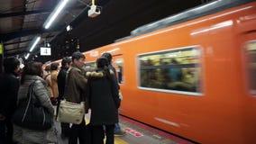 Väntande drev för folk på gångtunnelstationen ankommande drev arkivfilmer