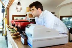 Väntande kunder för stilig ung kock på en matlastbil Arkivfoto