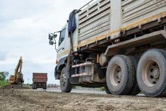 Väntande lastbil för en backhoe arkivfoto