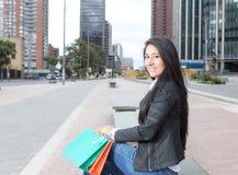Väntande latinsk kvinna med två shoppingpåsar Royaltyfri Fotografi