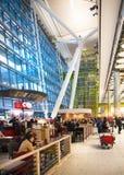 Väntande på ankomster för folk i Heathrow flygplatsterminal 5, London arkivfoton