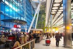 Väntande på ankomster för folk i Heathrow flygplatsterminal 5, London royaltyfria foton
