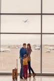 Väntande på avvikelse för familj på flygplatsen arkivfoton
