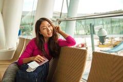 Väntande på avvikelse för ung lycklig flicka i internationell flygplats arkivbilder