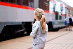 Väntande på drev för liten flicka på järnvägsstationplattformen Arkivfoton