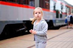 Väntande på drev för liten flicka på järnvägsstationplattformen Royaltyfria Foton