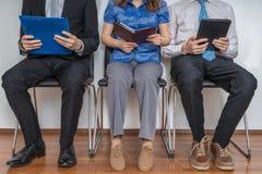 Väntande på intervju för grupp människor i ett väntande rum royaltyfri bild