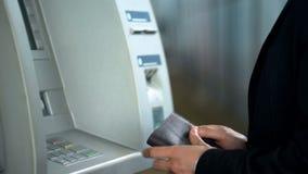 Väntande på kassa för affärsman från ATM, når att ha satt in kortet och att ha skrivit in stiftkod arkivfoto